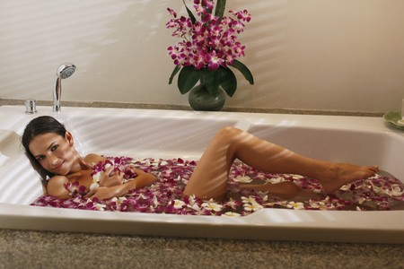bathtubs: Woman relaxing in bathtub with flower petals Stock Photo