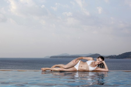 Woman lying on side at the edge of pool Stock Photo - 7595096