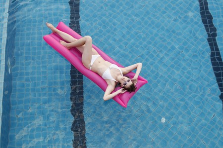 Woman relaxing on inflatable raft in pool photo