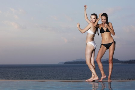 Women posing at the edge of pool photo