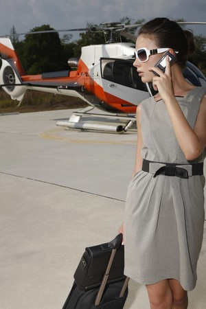 Businesswoman with luggage and briefcase talking on the phone at helipad photo