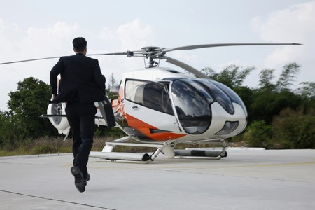 Businessman running towards helicopter