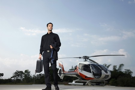 helipad: Businessman with briefcase standing at helipad, helicopter in the background Stock Photo