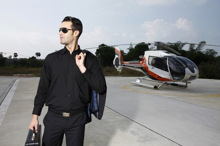 Businessman with briefcase standing at helipad, helicopter in the background Stock Photo - 7595318