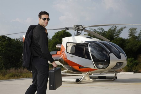 Businessman with briefcase walking towards helicopter Stock Photo - 7594981