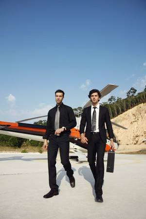 southeastern european descent: Businessmen walking away from helicopter