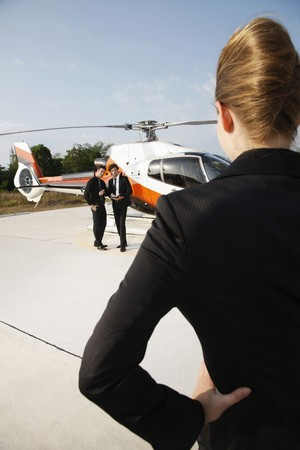 Businesswoman looking at businessmen standing by the helicopter photo