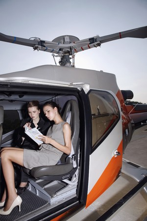 Businesswomen reading in helicopter Stock Photo - 7595576