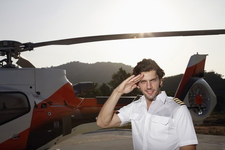 turkish ethnicity: Pilot saluting and standing in front of helicopter Stock Photo