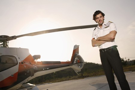 Pilot standing beside a helicopter photo
