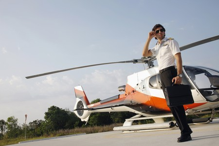 Pilot standing in front of a helicopter photo