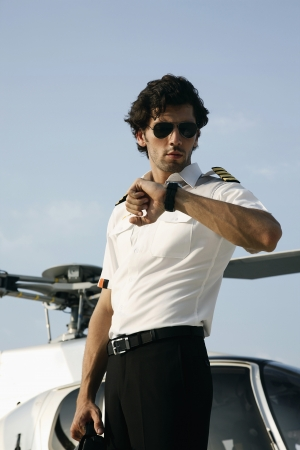 Pilot looking at his watch with helicopter in the background Banco de Imagens