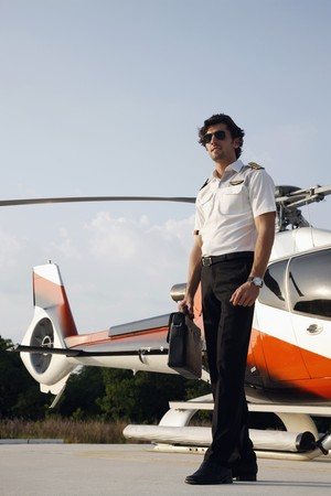 Pilot holding briefcase with helicopter in the background photo