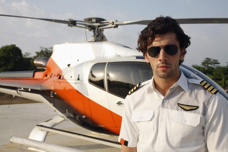 Pilot wearing sunglasses standing in front of helicopter photo