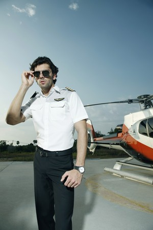 Pilot putting on sunglasses with helicopter in the background photo
