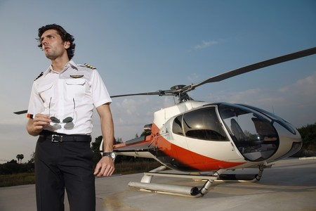 turkish ethnicity: Pilot holding sunglasses with helicopter in the background Stock Photo