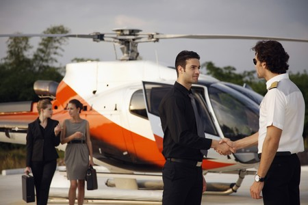 corporate image: Businessman shaking hands with pilot, businesswomen are walking from helicopter in the background