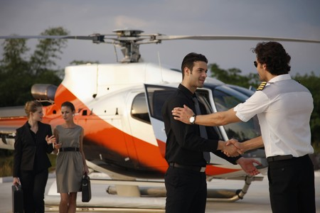 corporate image:  Businessmen shaking hands while businesswomen are walking from helicopter in the background
