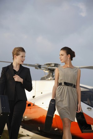 Businesswomen holding briefcase walking away from helicopter photo