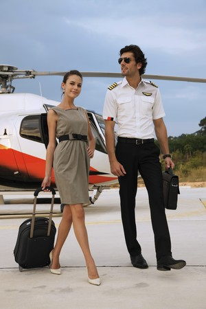 helicopter pilot: Businesswoman walking away from helicopter with pilot
