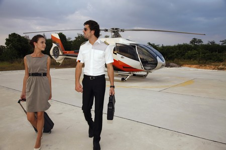 Businesswoman walking away from helicopter with pilot photo