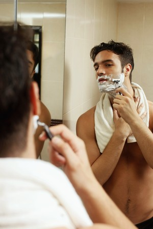 Man shaving in front of mirror photo