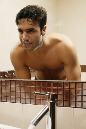 Man washing his face after shaving photo
