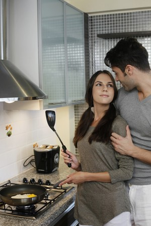 Man standing behind woman while she is preparing breakfast in kitchen Stock Photo - 7595689