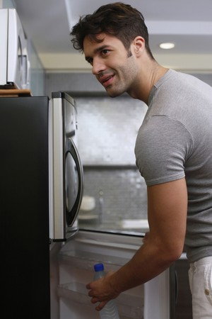 Man taking bottle water from refrigerator photo