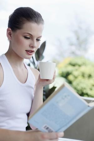 donna che beve il caff�: Donna bere caff� durante la lettura di un libro  Archivio Fotografico