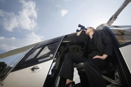 Businesswoman looking through binoculars from helicopter Stock Photo - 7594864
