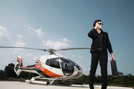 turkish ethnicity: Businessman standing at helipad with helicopter in the background