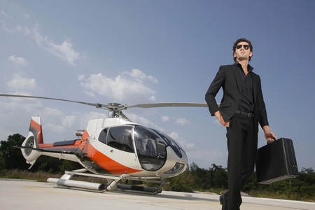 Businessman holding briefcase walking away from helicopter Foto de archivo