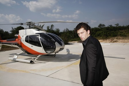 Businessman walking towards helicopter photo