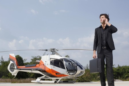 Businessman talking on the phone with helicopter in the background Stock Photo - 7594967
