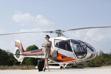 ukrainian ethnicity: Businesswoman with luggage and briefcase walking away from the helicopter