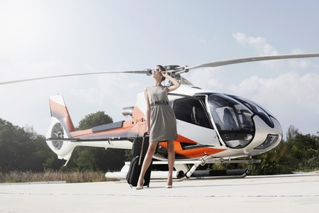 Businesswoman with luggage and briefcase standing in front of the helicopter photo