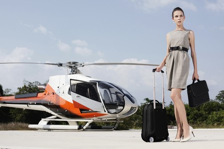 Businesswoman with luggage and briefcase standing at helipad photo