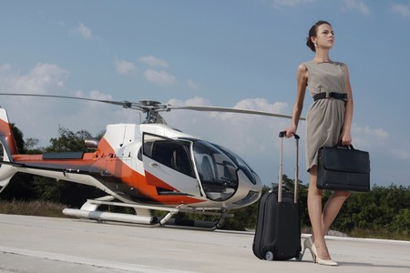 helipad: Businesswoman with luggage and briefcase standing at helipad Stock Photo