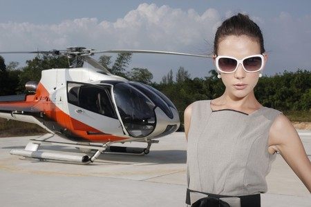 Businesswoman wearing sunglasses with helicopter in the background photo