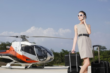 helipad: Businesswoman with luggage and briefcase at helipad, talking on the phone Stock Photo