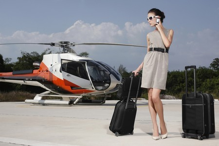 Businesswoman with luggage and briefcase at helipad, talking on the phone photo
