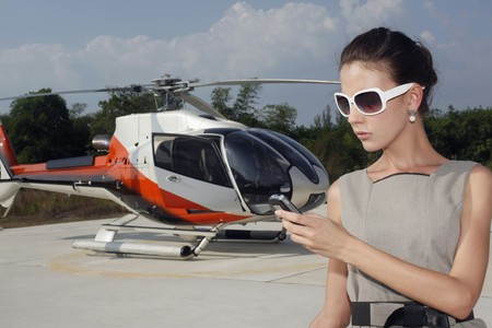 Businesswoman with luggage and briefcase at helipad, text messaging photo