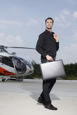 helipad: Businessman holding briefcase standing at helipad Stock Photo