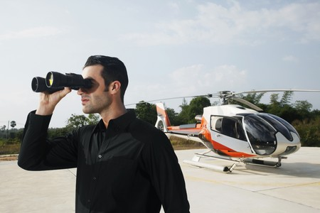 Businessman looking through binoculars at helipad photo