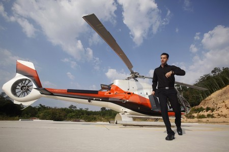 Businessman looking at watch while walking away from helicopter photo