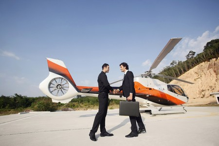 Businessmen shaking hands with helicopter in the background photo