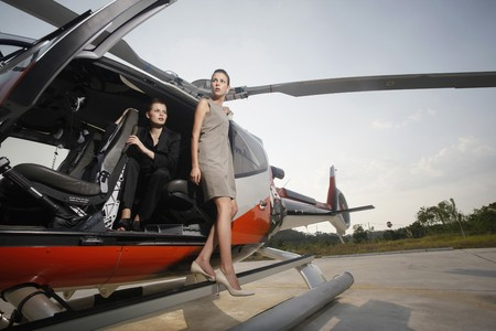 Businesswomen stepping out of helicopter Stock Photo - 7595306