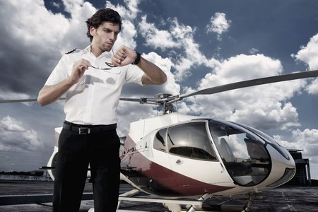 helicopter pilot: Pilot looking at his watch with helicopter in the background Stock Photo