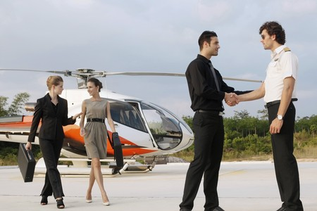 Businessmen shaking hands with pilot while businesswomen are walking away from helicopter Stock Photo - 7595194